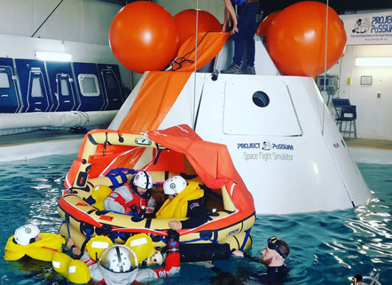 Project PoSSUM members test Final Frontier space suits through unassisted top-hatch egress procedures in a test article approximating NASA's Orion spacecraft.