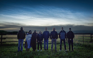 The 2017 PoSSUM 'Blue Jet' team stands under an intense noctilucent cloud display.